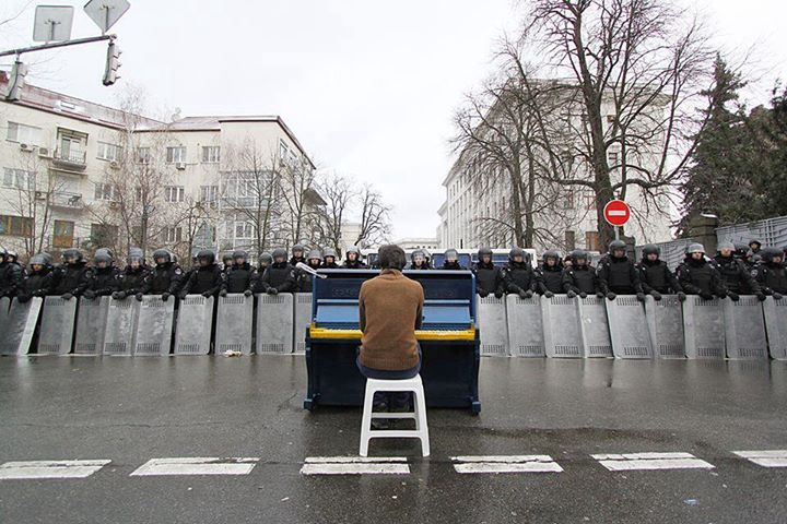 A protester playing piano conftonting riot police